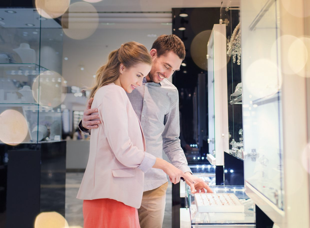 Photo of happy couple shopping for a diamond engagement ring together