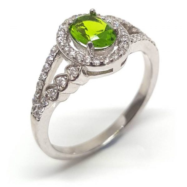 Feminine and stylish, this citrus leaf yellow-green coloured central stone dress ring of approx. 10mm top width will make you feel truly special. Features a 0.76 carat oval cut and shape peridot coloured cubic zirconia (7mm x 5mm) central stone in a 4-prong setting. Accented with a surrounding halo and a striking split shank band with further glittering white cubic zirconia stones. The split shank tapers to a 2mm wide band at the base and these dress rings have an approx 2.5 gram overall weight. This finest quality rhodium plated 925 sterling silver jewellery will add sparkle to any outfit.