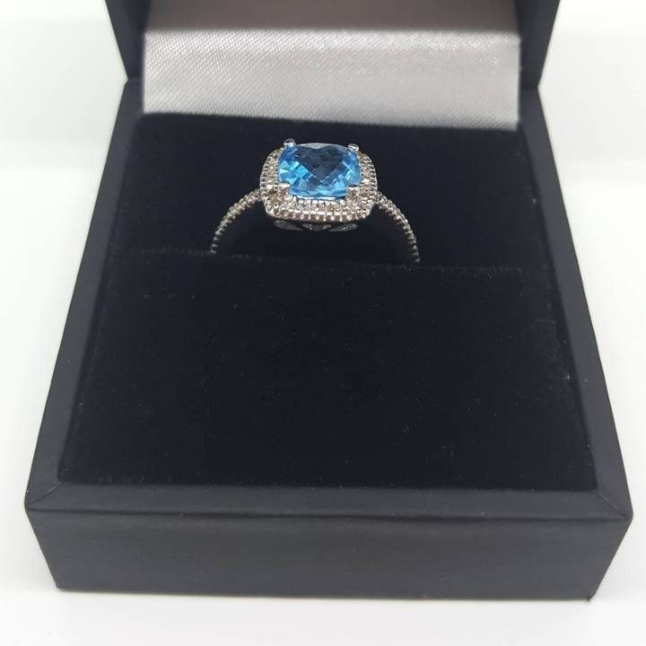 Luxuria Blue topaz engagement rings featuring a natural semi-precious blue topaz gemstone, this December birthstone ring with halo is an elegant, timeless choice